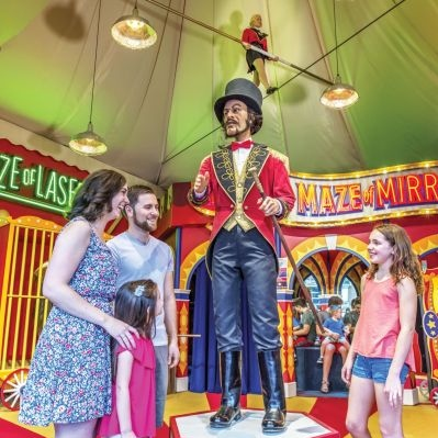 Family standing by ringmaster statue at Midway